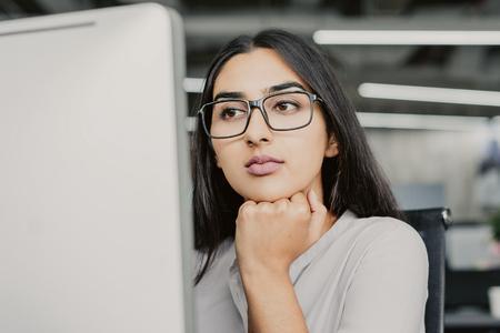 コンピュータで働く眼鏡をかけた真面目な若いラテンアメリカ人ビジネスウーマンの肖像画、あごに手を置いてモニターを見ている集中した女性マネージャー 写真素材 - 101488467