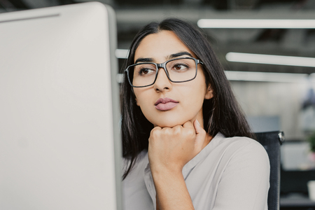 Portrait of serious young Latin-American businesswoman wearing eyeglasses working at computer, concentrated female manager looking at monitor with hand on chin