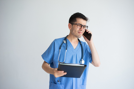 Tensed young male doctor talking on smartphone. Communication and medicine concept. Isolated front view on white background. Stock Photo