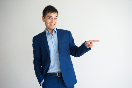 Excited young business man pointing finger aside. Promotion concept. Isolated front view on white background.
