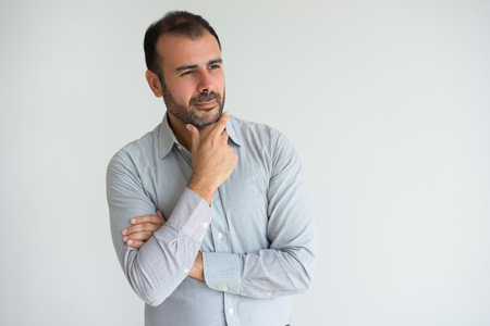 Portrait of pensive mid adult businessman with hand on chin. Concentrated Caucasian bearded man wearing striped blue shirt thinking about something. Concentration and planning concept Stock Photo