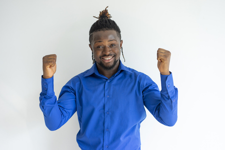 Cheerful successful black guy making yes gesture and looking at camera. Happy excited young businessman with afro hairstyle gesturing in ecstasy. Winning concept