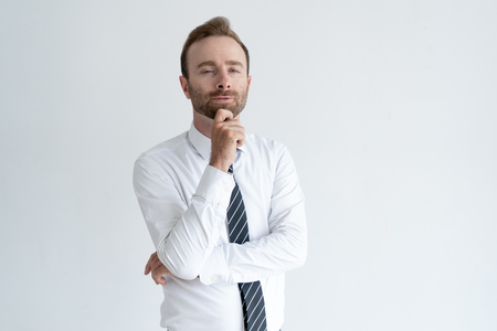 Sneaky business man touching chin, thinking and looking at camer Stock Photo