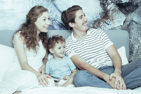 Happy family with son sitting together on bed