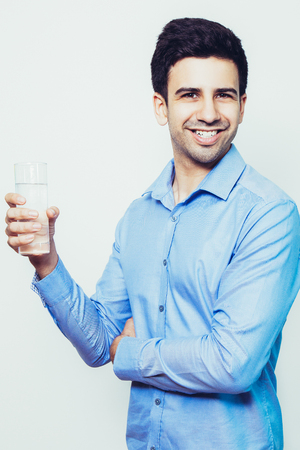 Happy Young Handsome Man Holding Glass of Water Foto de archivo