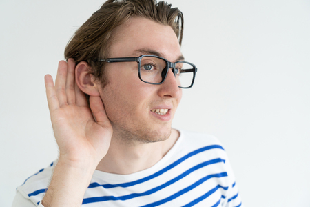 Positive young man in glasses eavesdropping and holding hand near ear to listen better. Concentrated guy listening to privacy conversation. Rumor concept