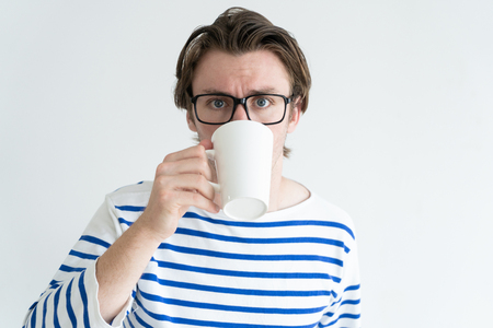 Scared frowning young man in glasses drinking coffee and looking at camera. Frightened guy in stripped sweater holding mug. Amazing concept