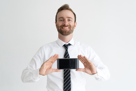 Smiling business man holding smartphone, showing its screen and looking at camera. Promotion concept. Isolated front view on white background. Reklamní fotografie