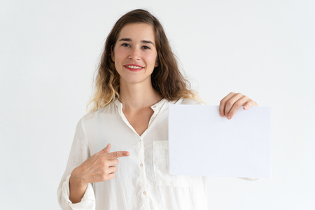 Smiling young woman holding blank sheet of paper, pointing at it and looking at camera. Promotion concept. Isolated front view on white background.