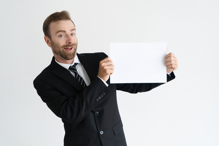 Cheerful young businessman presenting new information, offer, service. Positive Caucasian man in jacket and tie showing blank sheet of paper. Advertising and presentation concept