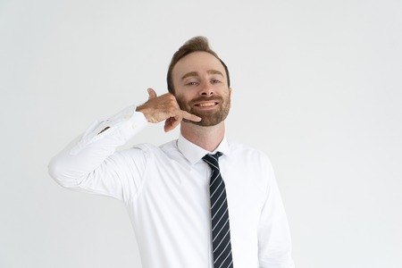 Broadly smiling businessman asking by gesture to phone him. Young Caucasian man in formal wear raising arm to ear and showing call me gesture. Communication or gesturing concept 免版税图像