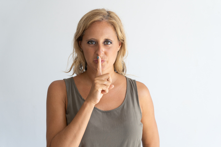 Portrait of mid adult blond-haired woman showing silence gesture. Caucasian woman standing with hand on lips. Secrecy and silence gesture