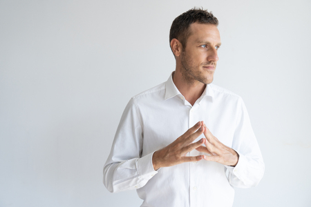 Concentrated mid adult businessman standing with joined fingers. Portrait of Caucasian man wearing white shirt looking away with pensive expression. Concentration and idea concept