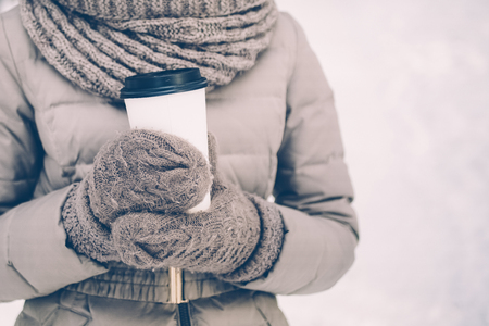 Close-up of woman in warm jacket holding take-away coffee in winter park. Smiling woman wearing scarf and mittens. She spending free time outdoors. Warming drink concept