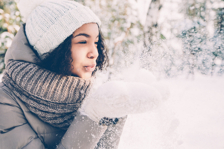 Portrait of happy teenage Latin American girl wearing white knit hat, scarf and jacket blowing snow off her hands in winter Stock fotó