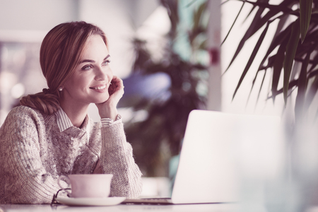Happy businesswoman sitting in cozy cafe. She leaning on hand and looking away. Pretty female manager working in co-working space. Smiling woman dreaming of love and happiness. Day dreaming concept
