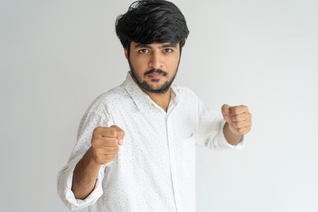 Serious brave Indian man with beard in fighting position. Confident handsome young man in casual shirt holding hands in fists and looking at camera. Battle concept Stock Photo