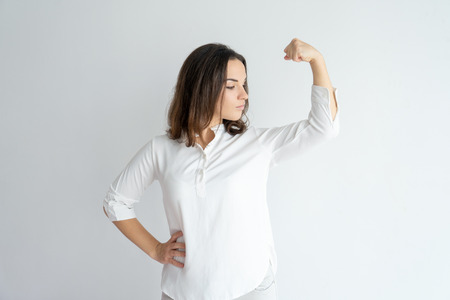 Serious proud girl showing strength gesture. Young Caucasian woman in white blouse flexing hand muscles and looking at bicep. Feminism concept Stock Photo
