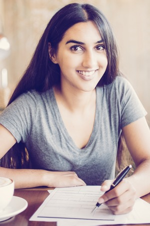 Diligent Indian student preparing for exam in cafe. Happy young woman working with papers and looking at camera. Positive student enjoying education. Doing homework concept Reklamní fotografie