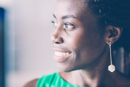 Close-up of face of young African American woman wearing earring, looking away and smiling