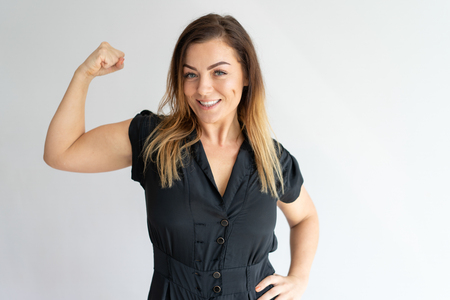 Positive joyful lady showing hand muscles. Middle aged Caucasian woman in casual wear flexing bicep. Strength or feminism concept