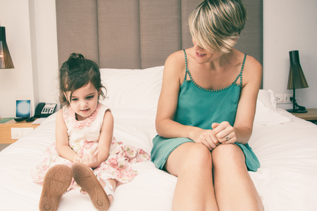 Little girl counting fingers and sitting on bed, mother observing her. Clever girl learning accounts or talking story to mom in bedroom. They sitting on bed. Simple mathematics concept