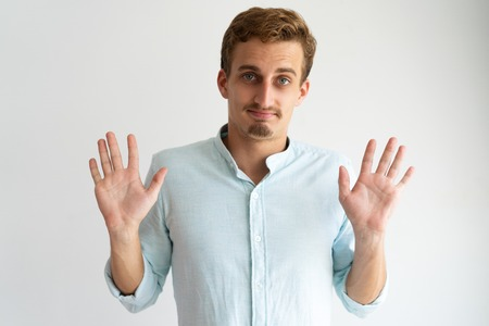 Friendly guy in white casual shirt gesturing Fine, You Won. Young Caucasian blonde man raising hands and showing palms in surrender gesture. Surrender concept Stock Photo