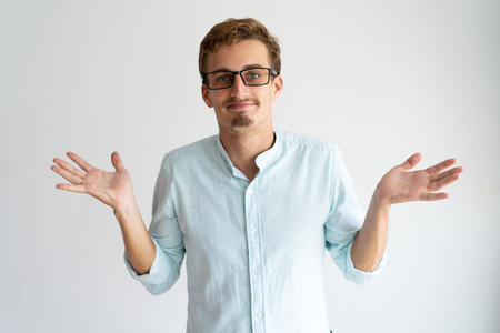 Smiling careless blonde guy showing do not know gesture. Young Caucasian man in glasses throwing up hands and shrugging shoulders. Nothing for it concept 写真素材