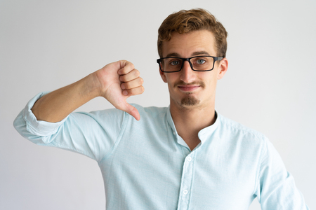 Smiling handsome guy in glasses expressing disapproval. Young Caucasian man in white casual shirt showing thumb down gesture. Dislike concept