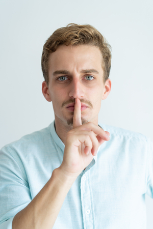 Serious young man looking at camera and making silence gesture. Handsome guy touching mouth with forefinger. Secret concept. Isolated front view on white background. Stock Photo