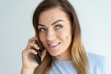 Smiling pretty woman talking on smartphone. Positive lady calling on mobile phone. Communication concept. Isolated front view on white background. 스톡 콘텐츠