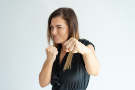 Positive athletic businesswoman punching at camera. Confident strong woman boxing while defending herself. Fighter concept