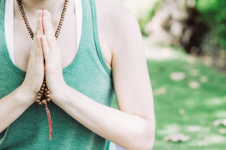 Young concentrated Caucasian woman wearing green tank top wearing rosary beads and praying or practicing yoga outdoors