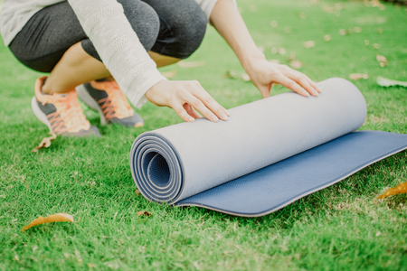 Hands of young Caucasian woman wearing sportswear crouching and rolling out exercise mat outdoors Stock Photo