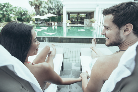 Closeup of young multi-ethnic couple looking at each other, holding hands and lying on chaise longues near swimming pool. They are back to camera.