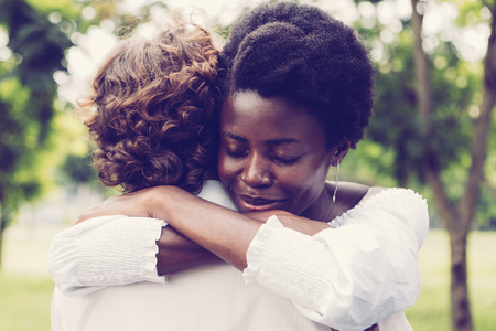 Portrait of young African-American woman embracing her Caucasian boyfriend and smiling in park
