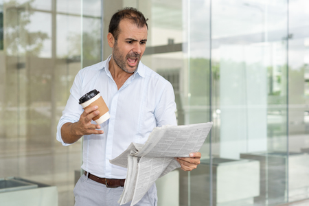 Furious business leader angry with negative review on his company. Mid adult Latin holding carton cup of coffee outdoors and yelling at newspaper. Bad news concept