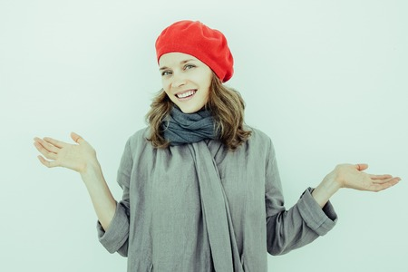 Cheerful young French woman expressing uncertainty and looking at camera. Smiling funny girl in red beret and scarf shrugging shoulders. Misunderstanding concept Stock Photo