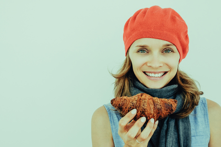 Closeup portrait of smiling young attractive woman holding croissant and looking at camera. Isolated front view on grey background.