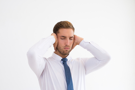 Stressed businessman covering ears with hands with his eyes closed. Tensed attractive guy. Stress concept. Isolated view on white background.