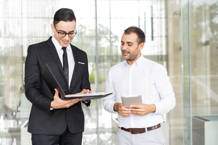 Portrait of smiling young consultant showing documents to client. Mid adult man with digital tablet meeting with banker or lawyer. Business relationship concept Banque d'images