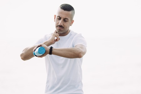 Concentrated male athlete taking pulse after running. Serious sporty young man holding fingers on neck and looking at wristwatch.  Feeling pulse concept