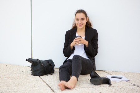 Cheerful young female employee fed up with office dress code. Stock Photo