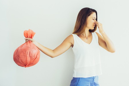 Displeased young woman with pinched face holding garbage bag and holding her nose. Unpleasant smell concept Stock Photo
