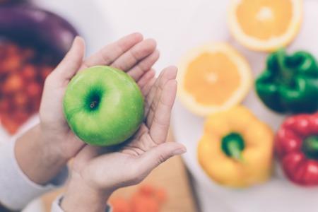 Primo piano delle mani femminili che tengono mela verde sopra il tavolo con le verdure Archivio Fotografico - 105514098