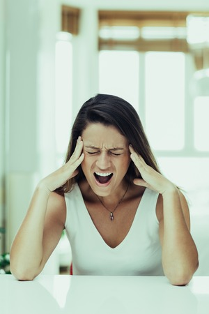 Stressful young woman crying from pain while sitting at table and leaning on it. Emotional businesswoman having problems at work. Crisis concept