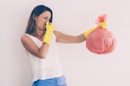 Unhappy woman holding trash with disgusting smell and holding nose to not feeling scent. Emotional young woman taking out trash. Garbage concept Imagens