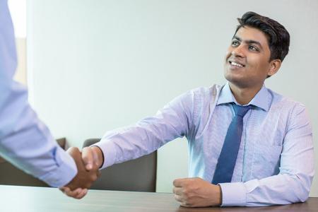 Socio de saludo empresario indio en la oficina. Líder empresarial y su socio irreconocible dándose la mano. Concepto de apretón de manos de negocios Foto de archivo