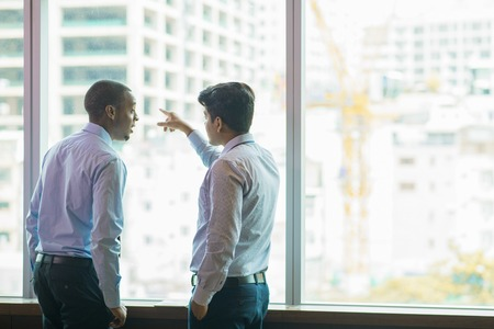 Construction company owners discussing ongoing project. Back view of Afro American businessman talking to Indian partner who pointing at building out of office window. Business talk concept