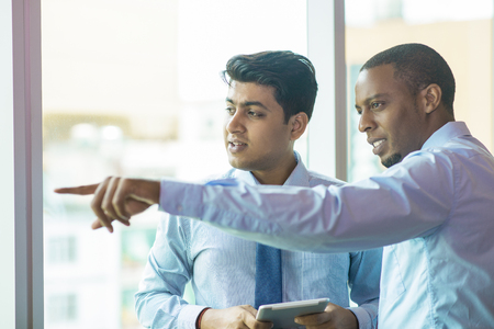 Mix raced business partners looking out window at neighbor construction. Afro American expert pointing out window and showing building to Indian colleague. Partnership concept Foto de archivo